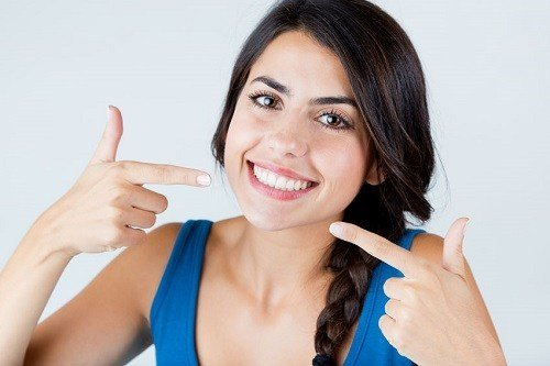 Young Woman Pointing On White Teeths
